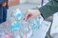 Image of Glass mason jars and someone donating money to a fundraiser