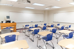 Image of rows of desks and chair in a class room in front of large white boards.