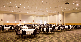 Image of a ballroom with round tables and chairs.