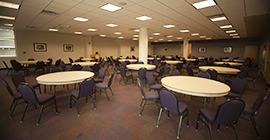 Image of a conference room with round tables and chairs.