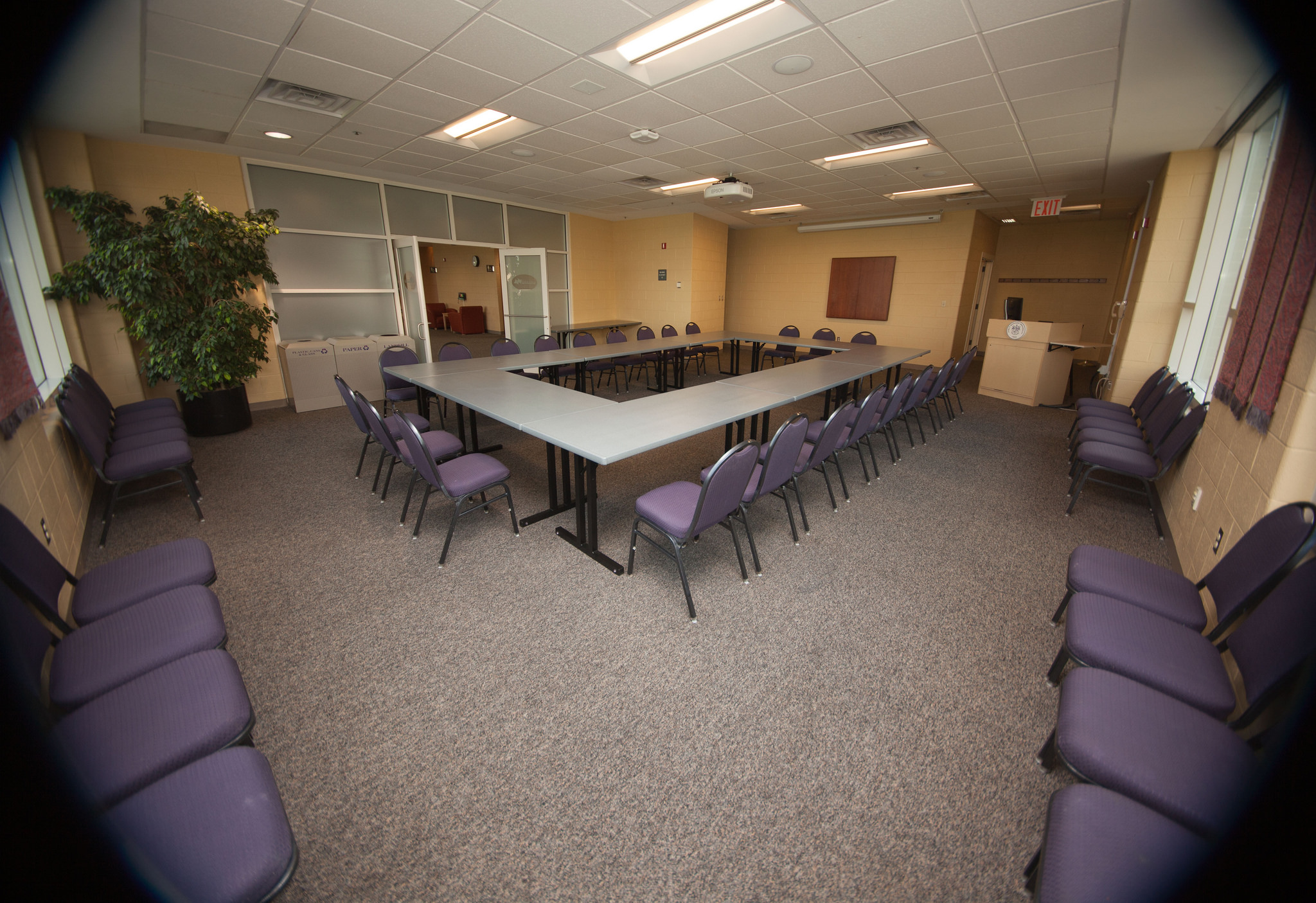 Image of a conference room with the tables forming a large rectangle.