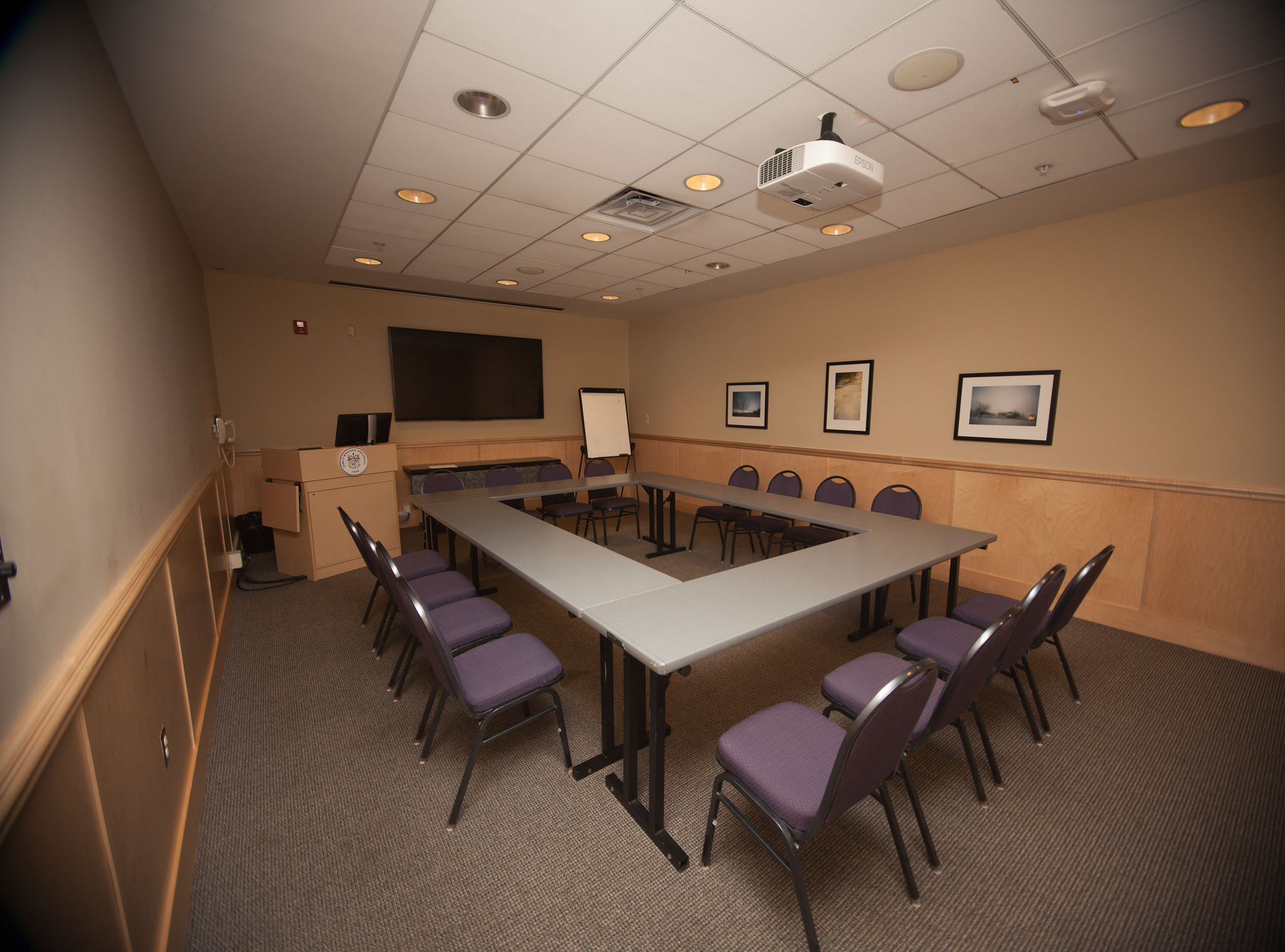 Photo of a small conference room with hollow square setup.