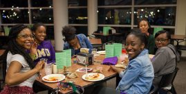 A group of students share a meal at a dining table in Festival Conference and Student Center at James Madison University.