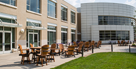 Image of a patio with tables and chairs outside of a modern building