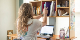 image of woman grabbing books from shelf above desk