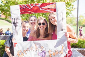 Image of a group of students posing behind a sign that reads, 'Greeks heart food.'