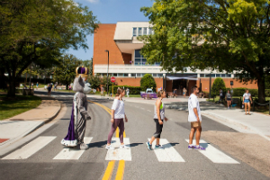 Image of three students and Duke Dog walking across a crosswalk