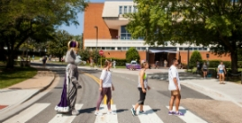 Image of duke dog and studnets walking in cross walk, abbey road style photo