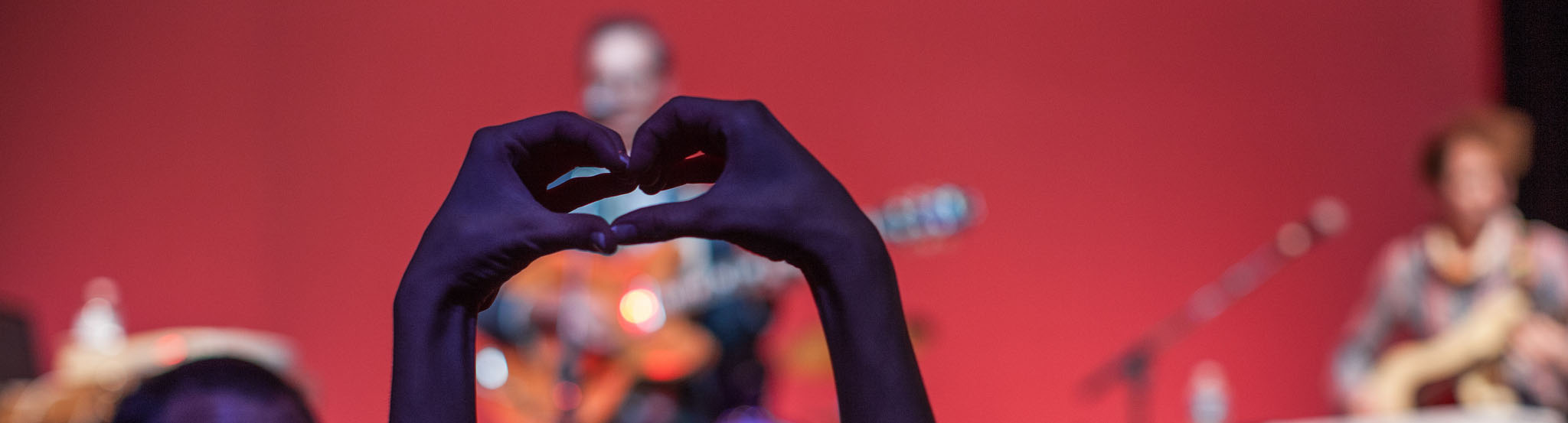Performers on a stage in the background. Hands making the shape of a heart in the foreground.