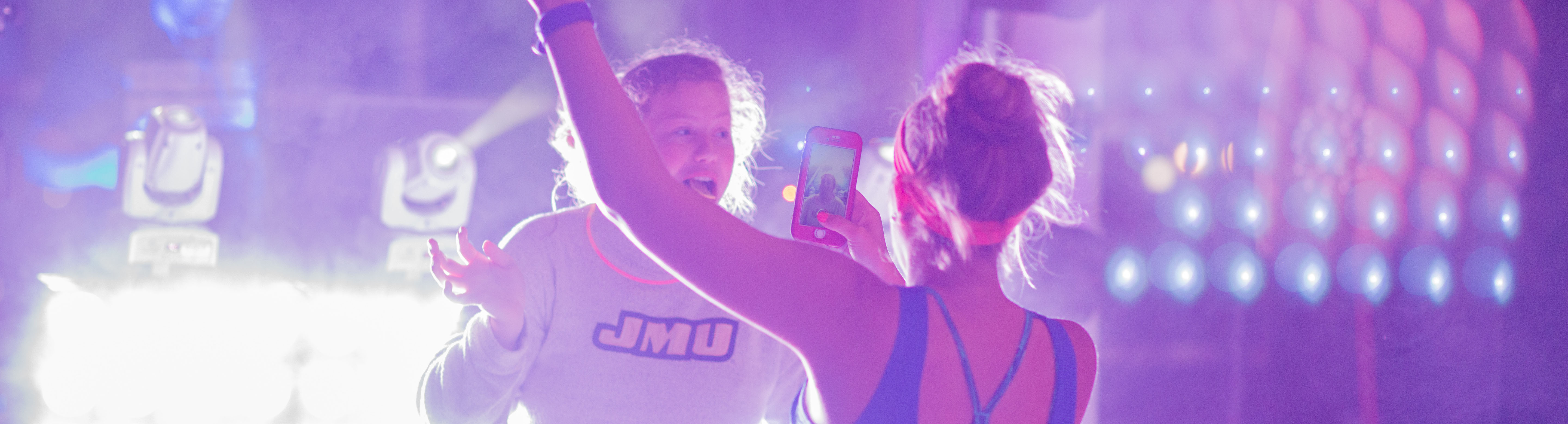 Two women, one taking a picture of the other with her phone during a concert.