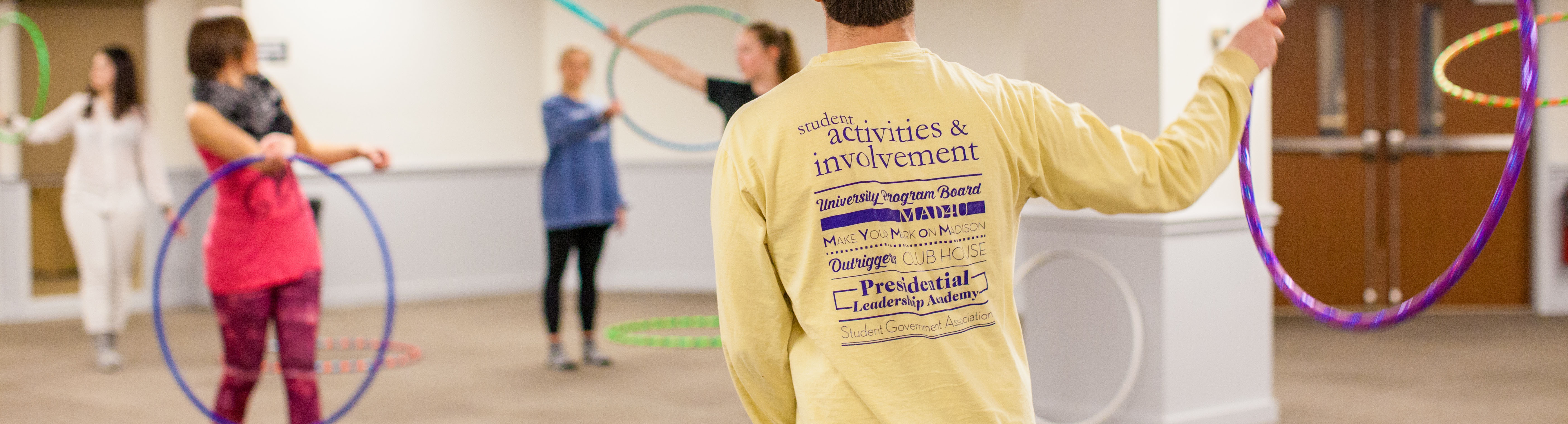 Young adults with hula hoops and the back of a persons JMU Student Activities & Involvement shirt in the foreground.