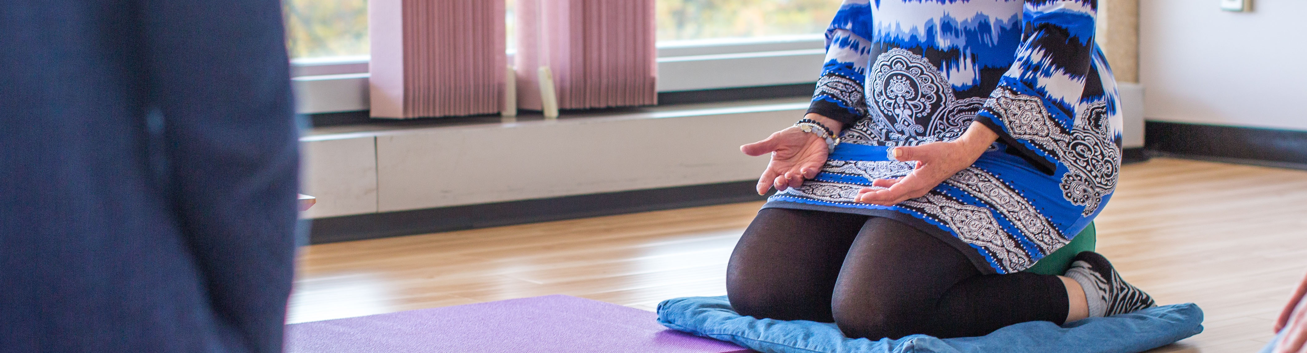 Bottom half of a person kneeling on a mat on the ground with hands facing upwards, meditating.