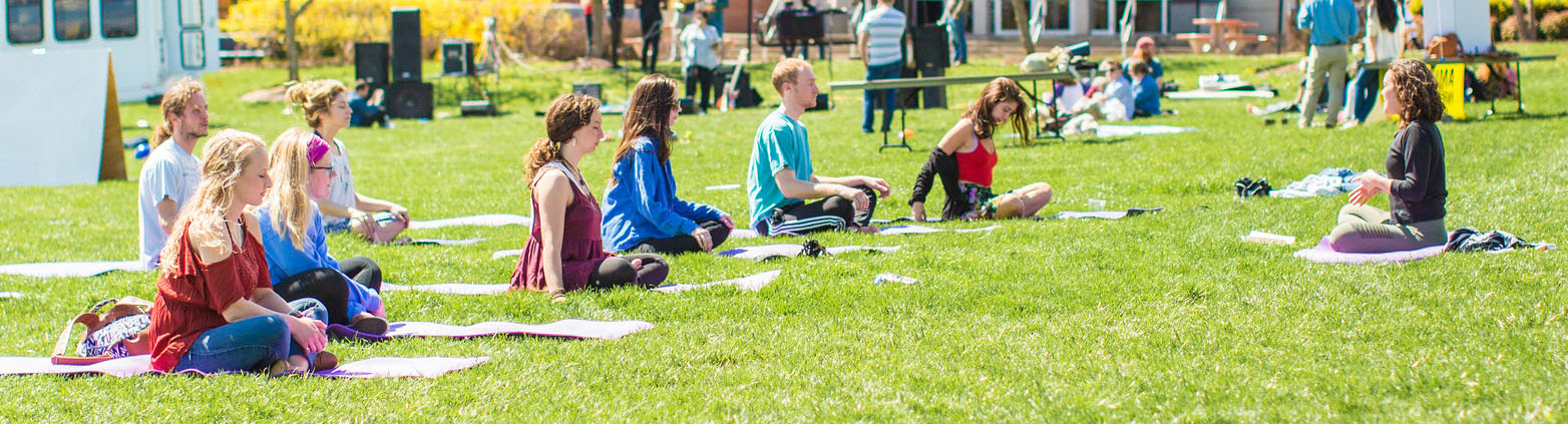 A group of nine sitting crossed leg on yoga mats outside on a sunny day.