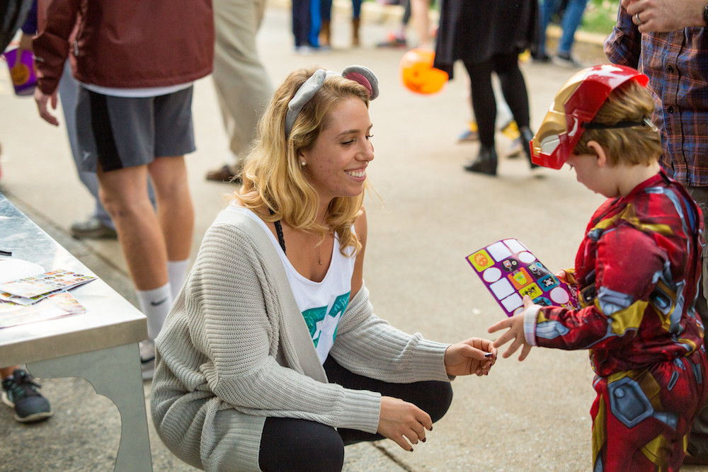 An image of a FSL sorority member giving candy to a small child.