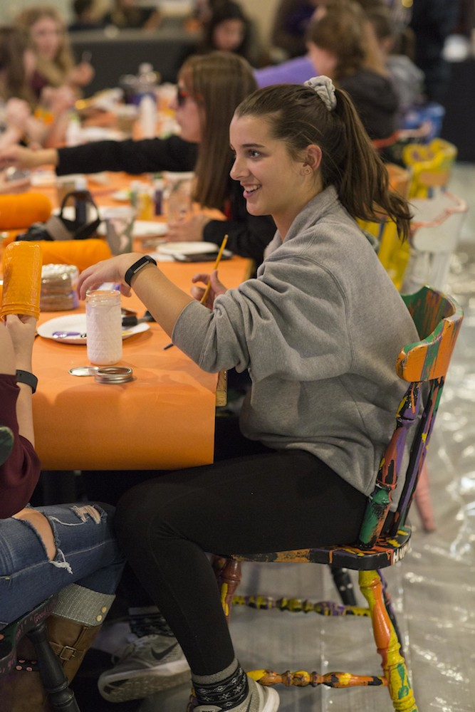 Image of a woman sitting at a student lounge table doing Halloween crafts.