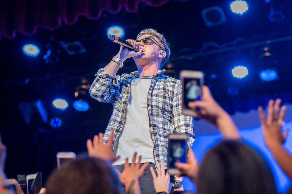 Image of Jesse McCartney performing while fans take photos with their phones.