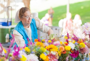 A woman gathers flowers for sale at the Farmer's Market.