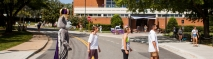 Four people, including the Duke Dog JMU mascot, walk across the crosswalk in front of Madison Union to replicate the Beatles album cover.