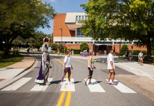 Image of four people, including the Duke Dog JMU mascot, walk across the crosswalk in front of Madison Union to replicate the Beatles album cover.