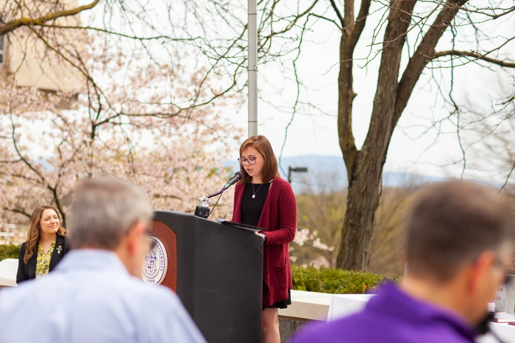 A woman speaks at a podium in front of a pink flower tree.