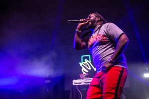 Image of T-Pain performs on stage in front of fog and blue backlighting.