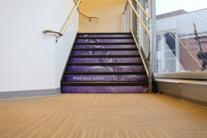 A stairwell covered in purple geometric graphics.