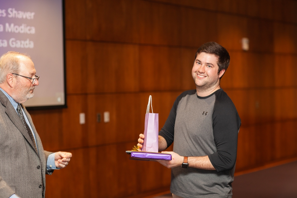 Tyler Owens receives an award in the Hall of Presidents at JMU.