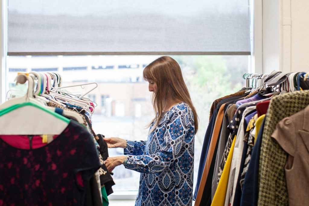 A woman looks through racks of professional clothing.