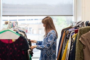 Image of a woman looks through racks of professional clothing.