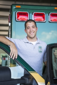 Image of a Volunteer Fire Fighter stands in front of his truck.