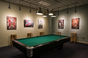Image of an art gallery in a student lounge behind a pool table.