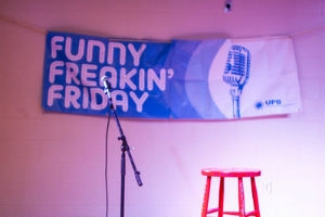 Image of the Funny Freakin' Friday banner behind a stool and microphone stand