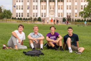 Image of four male students sitting on the quad at JMU