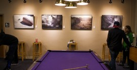 Picture of a pool table covered in royal purple felt, with student photography on the wall and college students hanging out nearby.