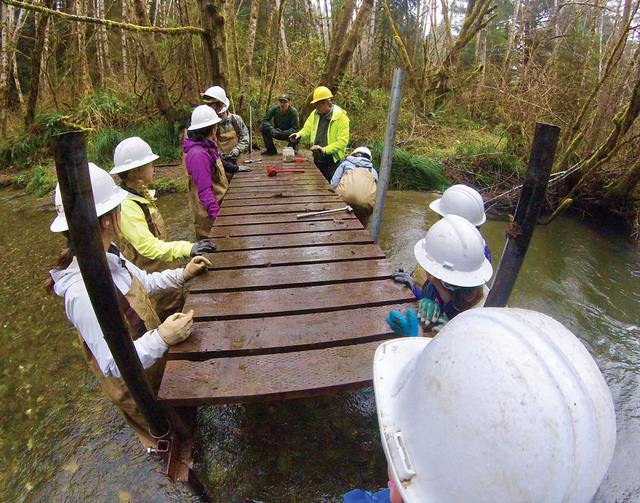 JMU students with hard hats on while constructing a bridge over a waterway.