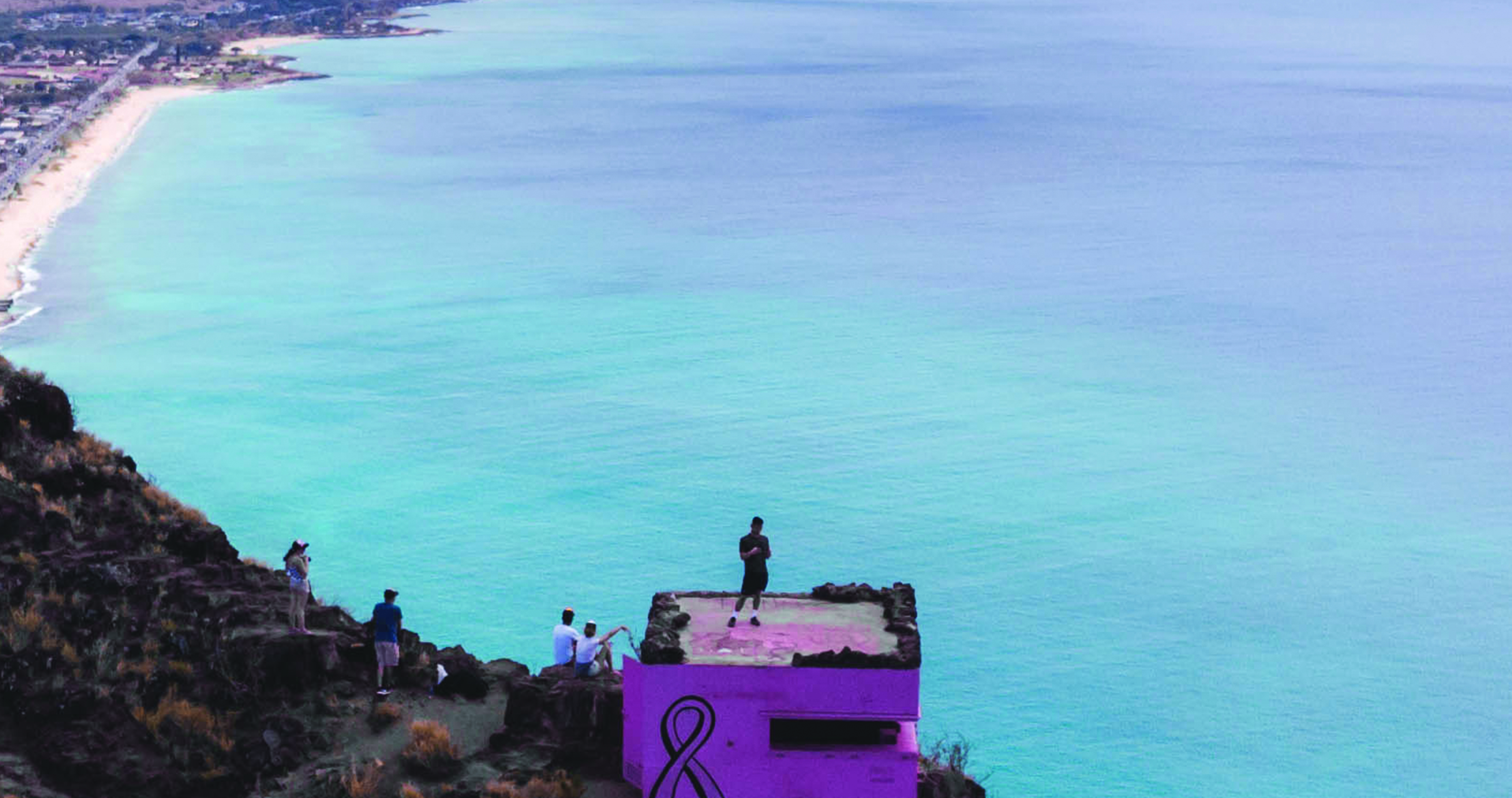 "The view from a hike in Hawaiian mountains which overlooks the bright blue ocean and people looking at the view from a ""pink pillbox"""