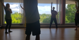 Image of students and a teacher raising their arms in front of a window with a view of trees.
