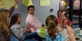 Image of 5 students in discussion around table. The two closest students have their hands raised.