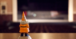 Gnorman, an orange garden gnome looks out over an empty auditorium.