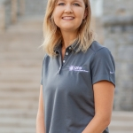 Photo of Katie Pomeroy, in a seated position wearing a grey UPB polo.