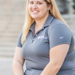 Photo of Katie Weems, in a seated position wearing a grey UPB polo