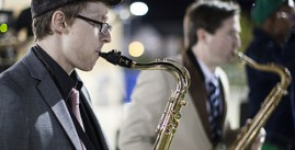 Image of two students playing saxophones outdoors at night.
