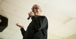 Image of a man with glasses speaking into a microphone