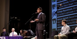 Image of a student giving a presentation on stage will other sit at tables around him.