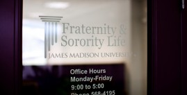 Image of a glass window with the Fraternity and Sorority Life logo written on it. It also reads, 'Office hours, Monday through Friday 9 to 5. Phone: 568-4195.'