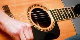 Image of a person playing a guitar.