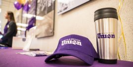 Image of a purple Madison union hat next to a silver Madison union mug on a purple table.
