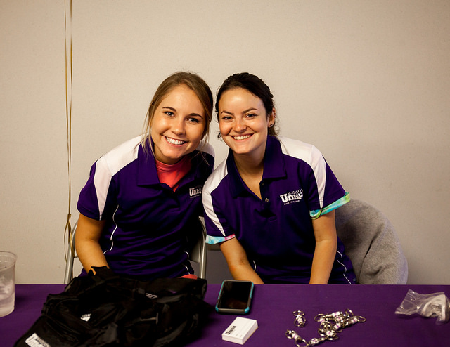 Two young women post for a picture at an information table.