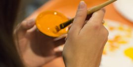 Image of a student painting a disc orange.