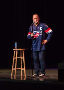 Dave Coulier stands on stage holding the mic stand.